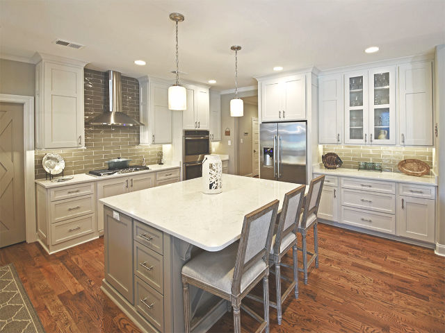 Spacious kitchen with white cabinetry stainless cooktop and vent and large island
